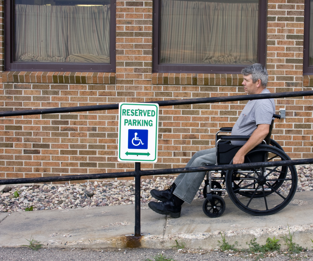 man in a wheelchair on a handicapped building ramp